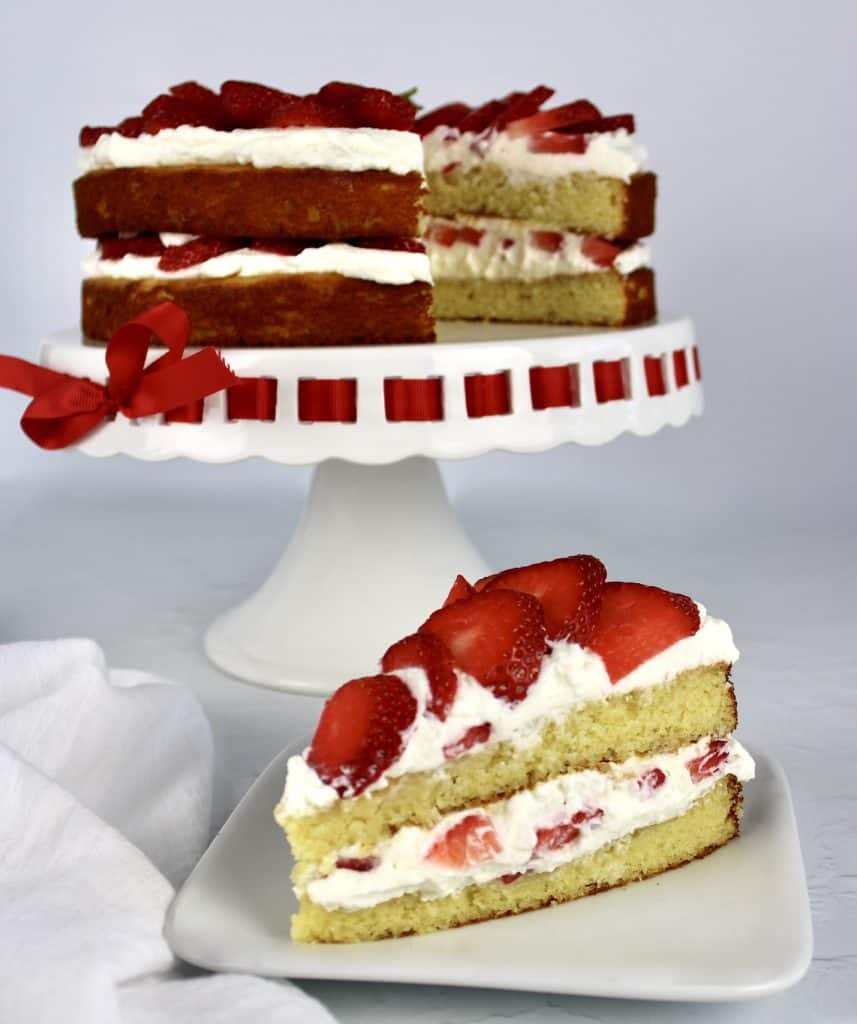 strawberry shortcake slice on white plate with rest of cake in background