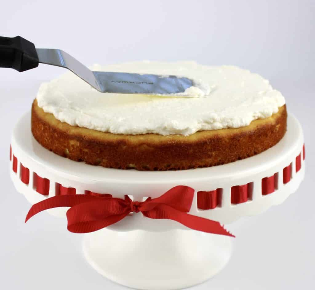 shortcake on cake stand with whip cream being spread on top