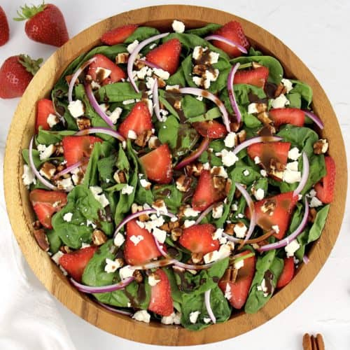 overhead view of strawberry spinach salad with dressing on top
