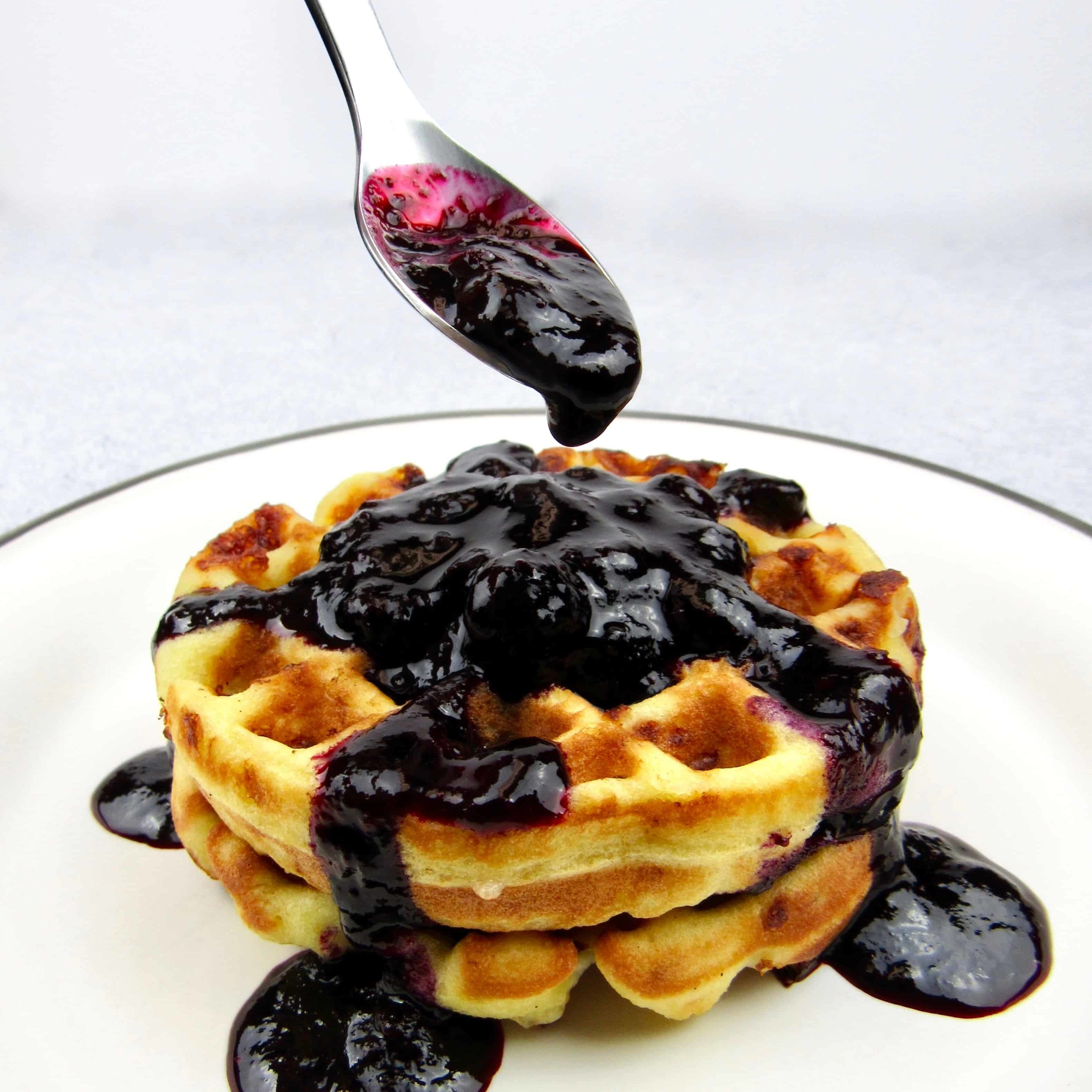 waffles wtih blueberry sauce dripping from spoon on top