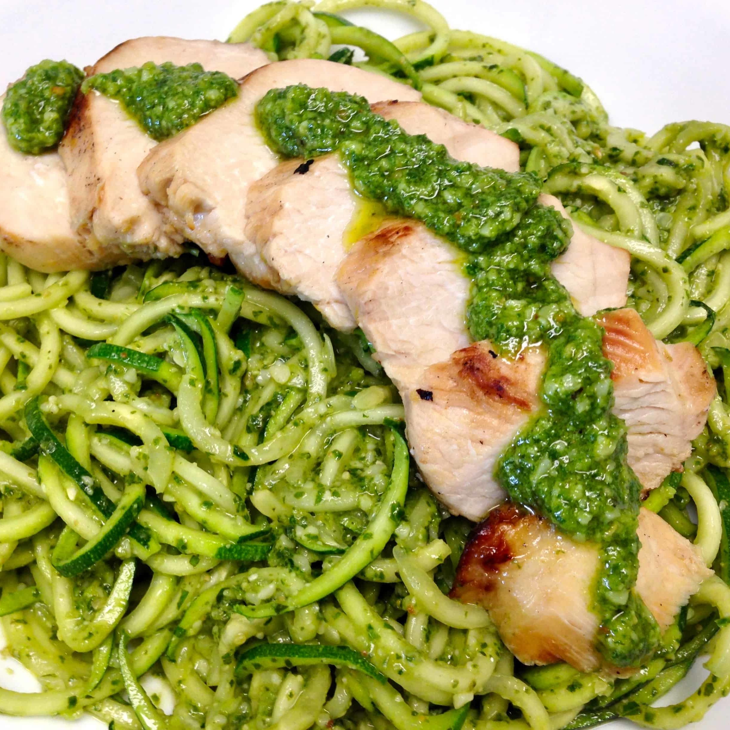 zucchini noodles with pesto sauce and sliced grilled chicken over the top